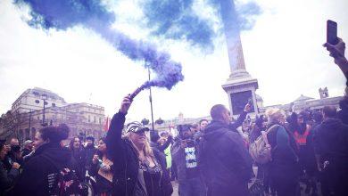 بريطاني يحمل قنبلة دخانية خلال مظاهرة ضد الإغلاق في لندن (رويترز)
